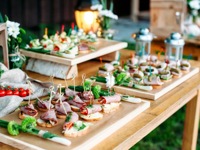 Beautiful catering banquet buffet table decorated in rustic style in the garden. Different snacks, sandwiches. Outdoor.